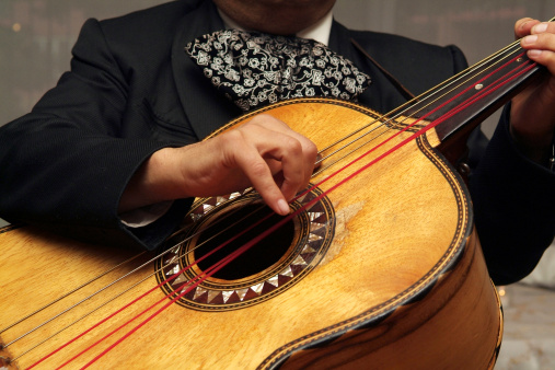 Close up of man's fingers strumming the strings of a mariachi guitar